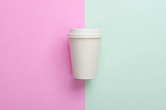Disposable takeaway take out coffee cup on light blue and pink Stock Images