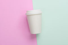 Disposable takeaway take out coffee cup on light blue and pink royalty free stock image