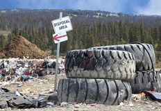 Disposal Area. Sign near a pile of large truck tires with piles of garbage in the background with trees and a blue sky Royalty Free Stock Photo
