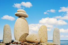 Dispose. Cobble-stones grouped on the shore of ocean on the background cloud Stock Photo