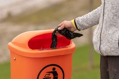 Dispose of stinking dogs shit properly. Woman does it royalty free stock image
