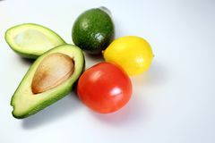 A disposição criativa é feita do abacate, do tomate e do limão Vegetais em um fundo branco Imagens de Stock Royalty Free