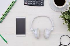 Disposição da tabela da mesa de escritório com fones de ouvido e smartphone imagem de stock