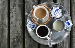 Disposição da tabela no café: copo de café, jarro de leite, açúcar Fotos de Stock Royalty Free