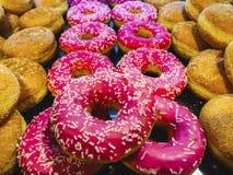 A disposição de açúcar polvilhou a filhós e a cor cor-de-rosa para o fundo fotos de stock royalty free