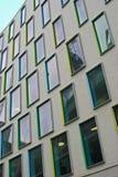 Disposição de janelas retangulares com quadros coloridos em amarelo, em verde, em ciano e em azul na fachada moderna cinzenta de  fotografia de stock