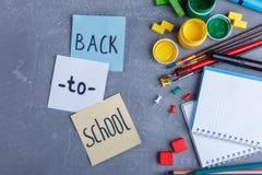 Disposição dos artigos de papelaria e dos alguns pedaços de papel com a inscrição de volta à escola O conceito da educação fotografia de stock royalty free