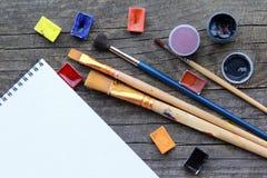 A disposição lisa do acrílico e da aquarela coloridos pinta, grupo de escovas e limita a zombaria branca da folha do álbum acima  Fotografia de Stock Royalty Free