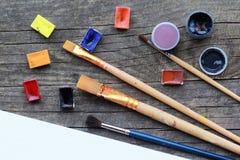 A disposição lisa do acrílico e da aquarela coloridos pinta, grupo de escovas e limita a zombaria branca da folha do álbum acima  Imagem de Stock Royalty Free
