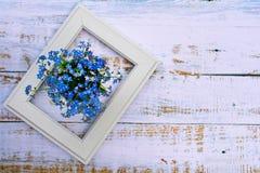 Disposi??o criativa com flores azuis e quadro branco em um fundo de madeira claro imagens de stock