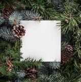 Disposición creativa hecha de las ramas de árbol de navidad con la nota de la tarjeta de papel, conos del pino Tema de Navidad y  fotografía de archivo