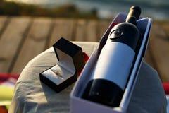 Disposición de la propuesta de matrimonio con un anillo en la copa de vino color de rosa y la botella fotos de archivo libres de regalías
