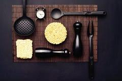 Disposición de los accesorios de la cocina y de los tallarines inmediatos en un fondo negro Visión superior Imágenes de archivo libres de regalías