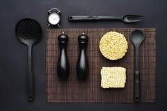 Disposición de los accesorios de la cocina y de los tallarines inmediatos en un fondo negro Visión superior Fotos de archivo