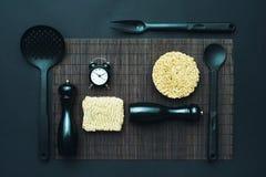 Disposición de los accesorios de la cocina y de los tallarines inmediatos en un fondo negro Visión superior Imagen de archivo libre de regalías