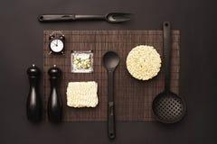 Disposición de los accesorios de la cocina y de los tallarines inmediatos en un fondo negro Visión superior Fotos de archivo libres de regalías