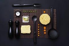 Disposición de los accesorios de la cocina y de los tallarines inmediatos en un fondo negro Visión superior Foto de archivo