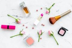 Disposición decorativa de los cosméticos Tonos rosados de la barra de labios, bulto, sombreador de ojos, perfume, cepillos entre  foto de archivo