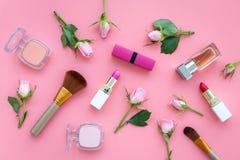 Disposición decorativa de los cosméticos Tonos rosados de la barra de labios, bulto, sombreador de ojos, perfume entre las flores imágenes de archivo libres de regalías