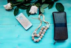 Disposición del fondo de la primavera en un fondo de madera azul con el monedero del teléfono de las flores y los accesorios colo Foto de archivo libre de regalías