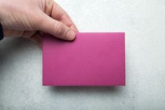 Disposición en blanco de una tarjeta de la invitación o de felicitación en púrpura a disposición en un fondo blanco del vintage imágenes de archivo libres de regalías