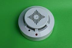 Dispositif d'alarme d'incendie en plastique rond blanc sur le mur vert Images stock