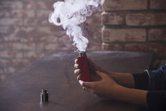 Dispositif de Vaping dedans dans la main du ` s de femme Photo stock