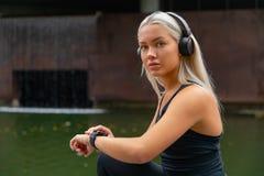 Dispositif intelligent de montre de forme physique d'établissement de femme pour le fonctionnement photo stock
