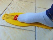 Dispositif jaune de mesure de pied avec le pied au moment photographie stock libre de droits