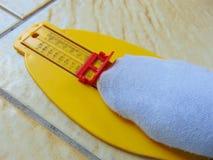 Dispositif jaune de mesure de pied avec le pied au moment photo stock