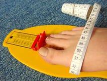Dispositif jaune de mesure de pied avec le pied nu au moment avec la bande de mesure photographie stock libre de droits