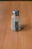Dispositif trembleur de poivre sur la table en bois Photographie stock libre de droits