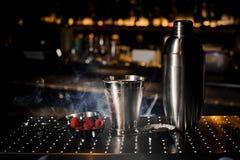 Dispositif trembleur en acier, tweezzers, tasse et soucoupe avec la framboise Image libre de droits