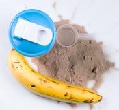 Dispositif trembleur, poudre de protéine et banane Photo stock