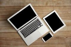 Dispositifs avec les écrans vides sur le fond en bois, photos stock