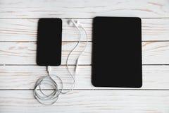Dispositifs de Digital avec des écouteurs sur un fond en bois blanc photographie stock