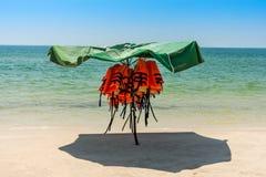 Dispositifs de flottaison personnels protégés contre le soleil sur un b vide images stock