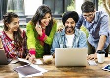 Dispositifs de technologie d'amis souriant à l'intérieur concept Photo stock
