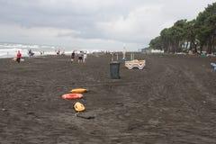 Dispositifs et lits pliants en plastique rouges de délivrance de flottaison sur la plage le temps est mat image libre de droits