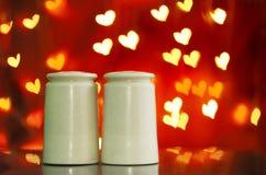 Dispositifs trembleurs de sel et de poivre avec le fond de bokeh de coeur Photographie stock libre de droits