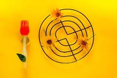 Disposition créative avec la brosse, la peinture et la fleur oranges de la marguerite des prés sur la texture-couleur jaune de l' images stock