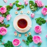Disposition créative de vue supérieure avec le lettrage de temps de thé avec les blocs en bois, tasse de thé chaud et fleurs rose Images libres de droits