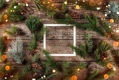 Disposition créative faite de branches de sapin de Noël avec le cadre des cônes de note et de pin de carte de papier sur le fond  photos libres de droits