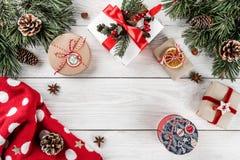 Disposition créative faite de branches de sapin de Noël, cônes de pin, cadeaux, chandail de Noël sur le fond en bois blanc image libre de droits