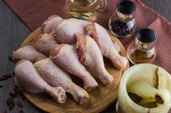 Disposition crue fraîche de jambes de poulet sur la planche à découper de cuisine Photo stock