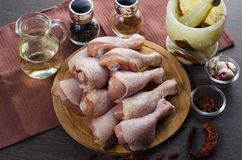 Disposition crue fraîche de jambes de poulet sur la planche à découper de cuisine Photos stock