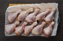 Disposition crue fraîche de jambes de poulet sur la planche à découper de cuisine Image libre de droits