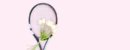 Disposition d'amour de tennis sur le fond rose en pastel avec la raquette de tennis avec les fleurs blanches de tulipes de bouque photographie stock libre de droits