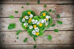 Disposition de coeur faite de feuilles et table rustique de fleurs Image libre de droits
