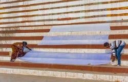 Disposition de deux personnes leur feuille blanche à sécher sur les banques du Gange Photographie stock